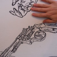 Scale picture of gun and artist's hand